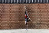 Full length side view of an African American man stretching against brick wall