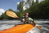 Portrait of a smiling young woman kayaking in the river