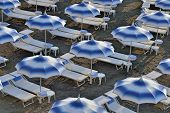Umbrellas and sunloungers on empty beach