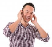 Attractive Asian man listening to mp3, isolated on white background, Asian male model.
