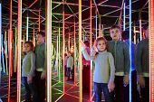 Boy and his younger sister wander in semidarkness of mirror labyrinth