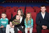 Parents with children watching a movie in the cinema