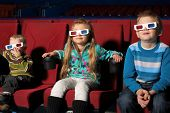 stock photo of cinema auditorium  - Three small children in 3D glasses watching a movie in the cinema - JPG