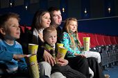 Friendly family watching a movie and eating popcorn in the cinema