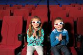 Two small children smiling in 3D glasses and clapping in the cinema