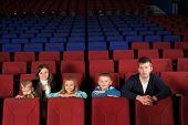 Parents with children watching a movie in empty cinema hall