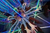 Boyl sits stretching his arms at crossing in mirror labyrinth illuminated with color lights