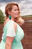 foto of aquamarine  - Blond young woman in an oversized aquamarine dress with matching earrings - JPG