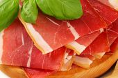 thin slices of parma ham with basil on a wooden plate