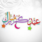 Arabic Islamic calligraphy of colorful text Eid Mubarak on floral decorated grey background.
