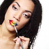 visagiste make-up artist draw rainbow vivid color lips with brush, face detail