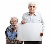 Senior woman and man holding a blank billboard