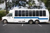 stock photo of motor coach  - White and Blue Unmarked Shuttle Bus Waiting for Passengers - JPG