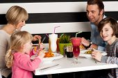Family Toasting Smoothies In Restaurant