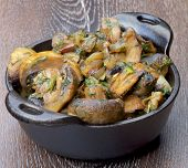 pic of stew pot  - Tasty Champignon Mushrooms Stew with Onion and Greens in Black Cast - JPG