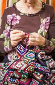 Hands of woman knitting a vintage wool quilt