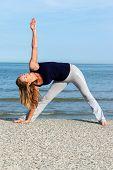 Athletic Woman Doing Yoga Training On The Beach