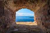 View Of Blue Sea Seascape From Hole Window Frame In Old Stone Wall