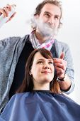 pic of hairspray  - Male coiffeur giving women hairstyling with hairspray in shop - JPG