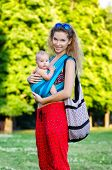 Young mother and baby in a sling. Outdoor.