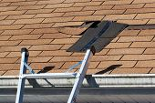 stock photo of hurricane wind  - Fixing damaged roof shingles - JPG