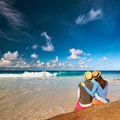 Couple on a tropical beach at Seychelles wearing rash guard