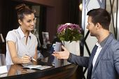 Happy receptionist and guest talking at hotel reception.