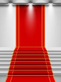 Stairs covered with red carpet with a spotlight.