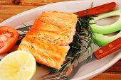 roast fish: hot grilled salmon over glass plate on over wooden table