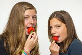 Two girls eating strawberries
