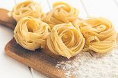 Italian pasta tagliatelle and flour on cutting board