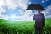 Mature businessman holding an umbrella against green field under blue sky