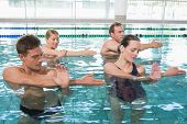 stock photo of day care center  - Happy fitness class doing aqua aerobics in swimming pool at the leisure centre - JPG