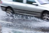 image of flood  - Car causes a large splash as it drives through a flood of rain water