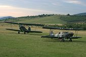 picture of biplane  - A vintage camouflage biplanes secured to the ground at a grassy airfield - JPG