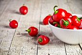 red hot peppers in bowl on rustic wooden background