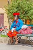 PERU, OLLANTAYTAMBO, MAY 4, 2014 - Woman in traditional folk costume sits on bench.