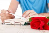 picture of poetry  - young man with his hands holding open book and leafing through pages while red rose and glasses are next to him focus on rose poetry reading - JPG