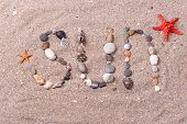 Word sun made from sea shells and stones on sand