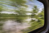 blurred abstract landscape of Missouri River seen from a train window in motion