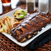 foto of baby back ribs  - bbq ribs with cole slaw and french fries shot with selective focus - JPG