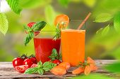 Fresh carrot and tomato juice, healthy drinks on wooden table.