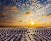 Wooden surface of planks pier under sunset dramatic sky