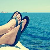 closeup of the feet of a man with flip-flops who is relaxing near the ocean in the summer, with a re