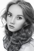 Black and white portrait of young beautiful woman with long curly hair and clean make-up