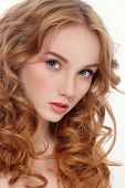 Portrait of young beautiful woman with long red curly hair and fresh make-up