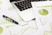Laptop And Pen With Green Business Charts, Graphs, Information And Reports