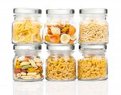 The Various Raw Pasta In A Glass Jar,  Isolated On White Background