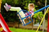 picture of swings  - Happy little girl swinging on playground area - JPG