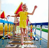 Image of cute girls having fun on playground outdoors